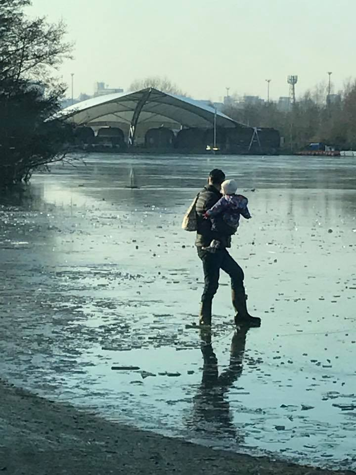 Man carries toddler across frozen lake