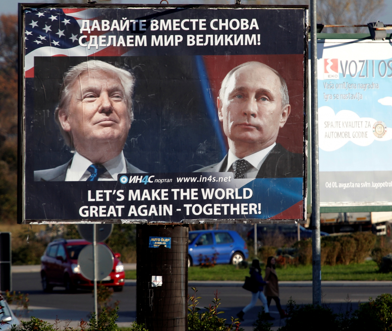 Pedestrians cross the street behind a billboard showing a pictures of US president-elect Donald Trump and Russian President Vladimir Putin in Danilovgrad, Montenegro,