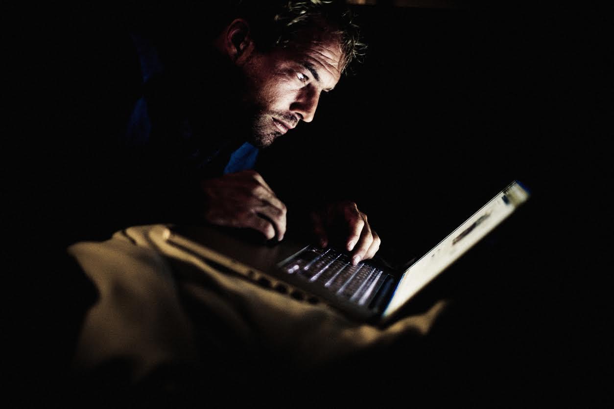 Man looking at laptop in the dark