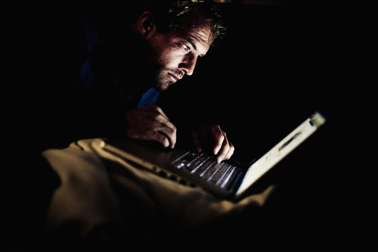 Man looking at laptop in the dark