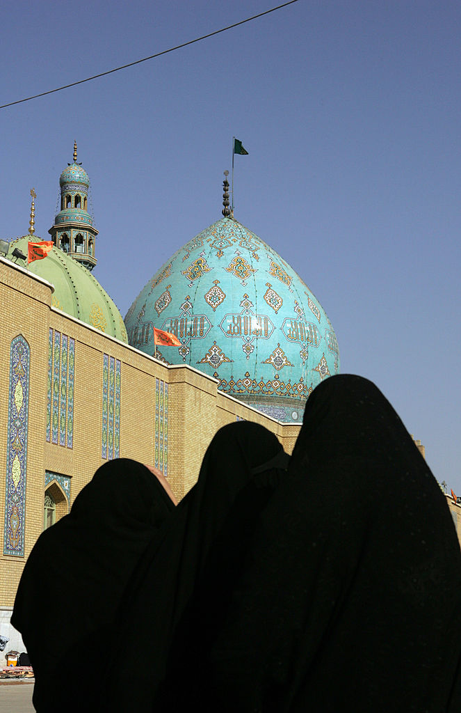 Iranian women walk in the courtyard of the Jamkaran mosque outside the religious city of Qom