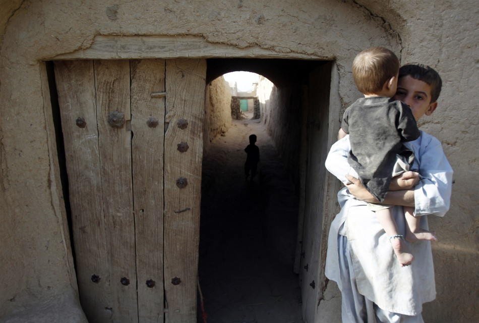 An Afghan boy holds a baby in the village of Small Loi Kola
