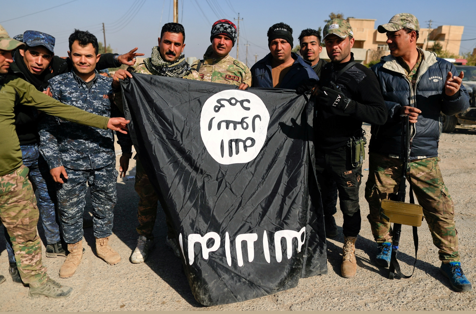 Iraqi security forces members pose with a seized Islamic State flag after driving out its miitants from Mosul's airport south west Mosul