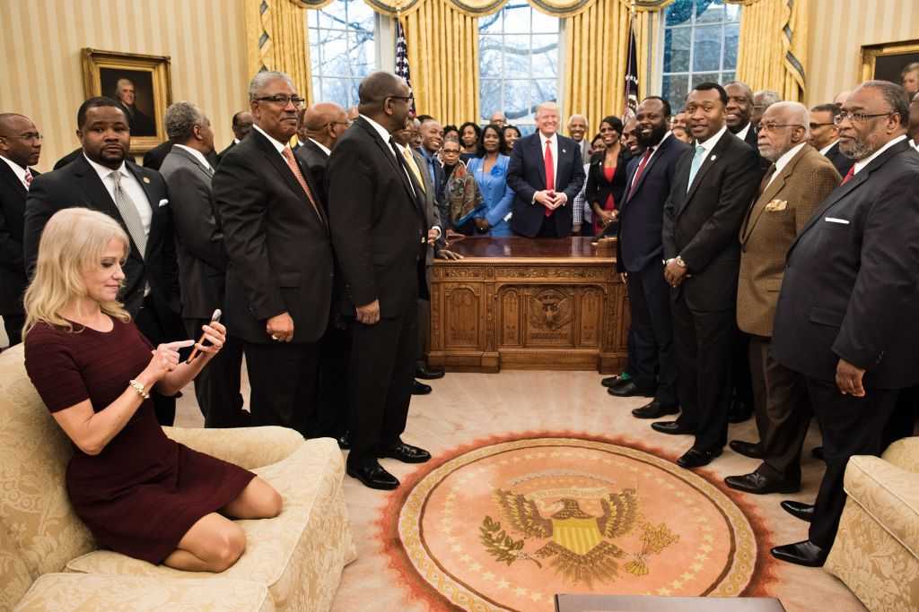Counselor to the President Kellyanne Conway (L) checks her phone after taking a photo as US President Donald Trump and leaders of historically black universities and colleges