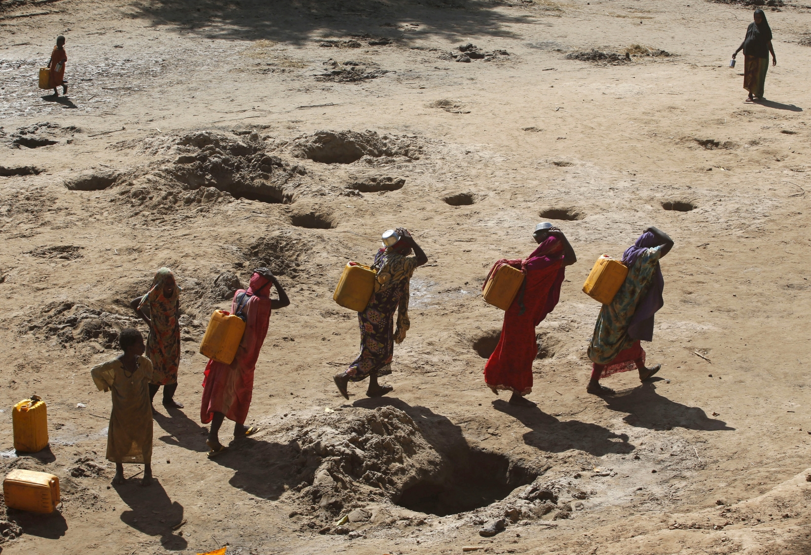 Women carry jerry cans of water