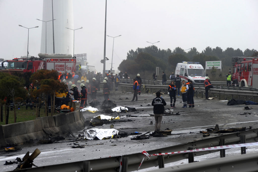 Firefighters work at the crash site of a helicopter as bodies lie covered with blankets in Istanbul on March 10, 2017