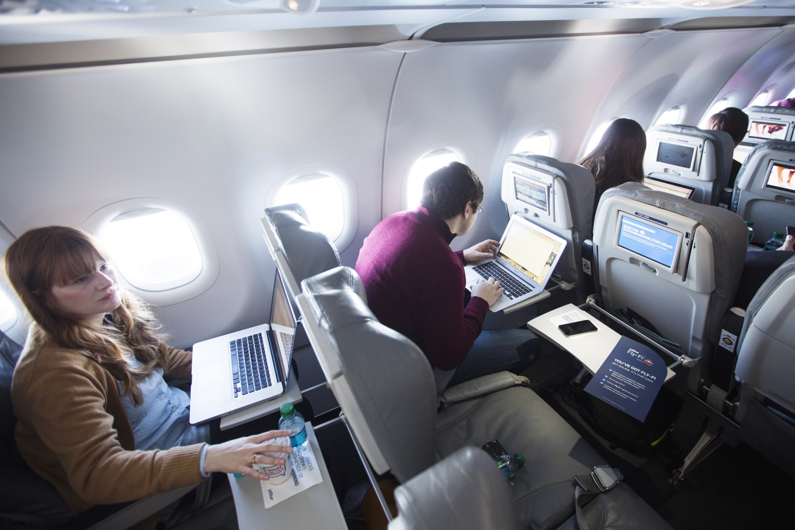 Journalists using laptops on wifi-equipped airplane