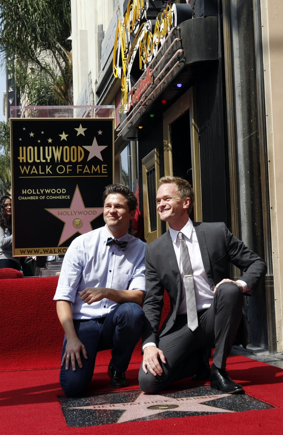 Actor Neil Patrick Harris (R) and his partner David Burtka pose together during ceremonies honoring Harris with a star on the Hollywood Walk of Fame in Hollywood September 15, 2011. The star was placed near the Frolic Room cocktail lounge sign background.