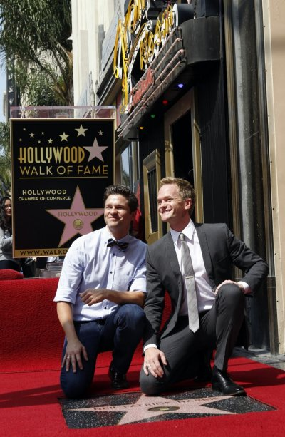Actor Neil Patrick Harris R and his partner David Burtka pose together during ceremonies honoring Harris with a star on the Hollywood Walk of Fame in Hollywood September 15, 2011. The star was placed near the Frolic Room cocktail lounge sign background.