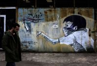 A man walks past a graffiti depicting a man throwing a petrol bomb