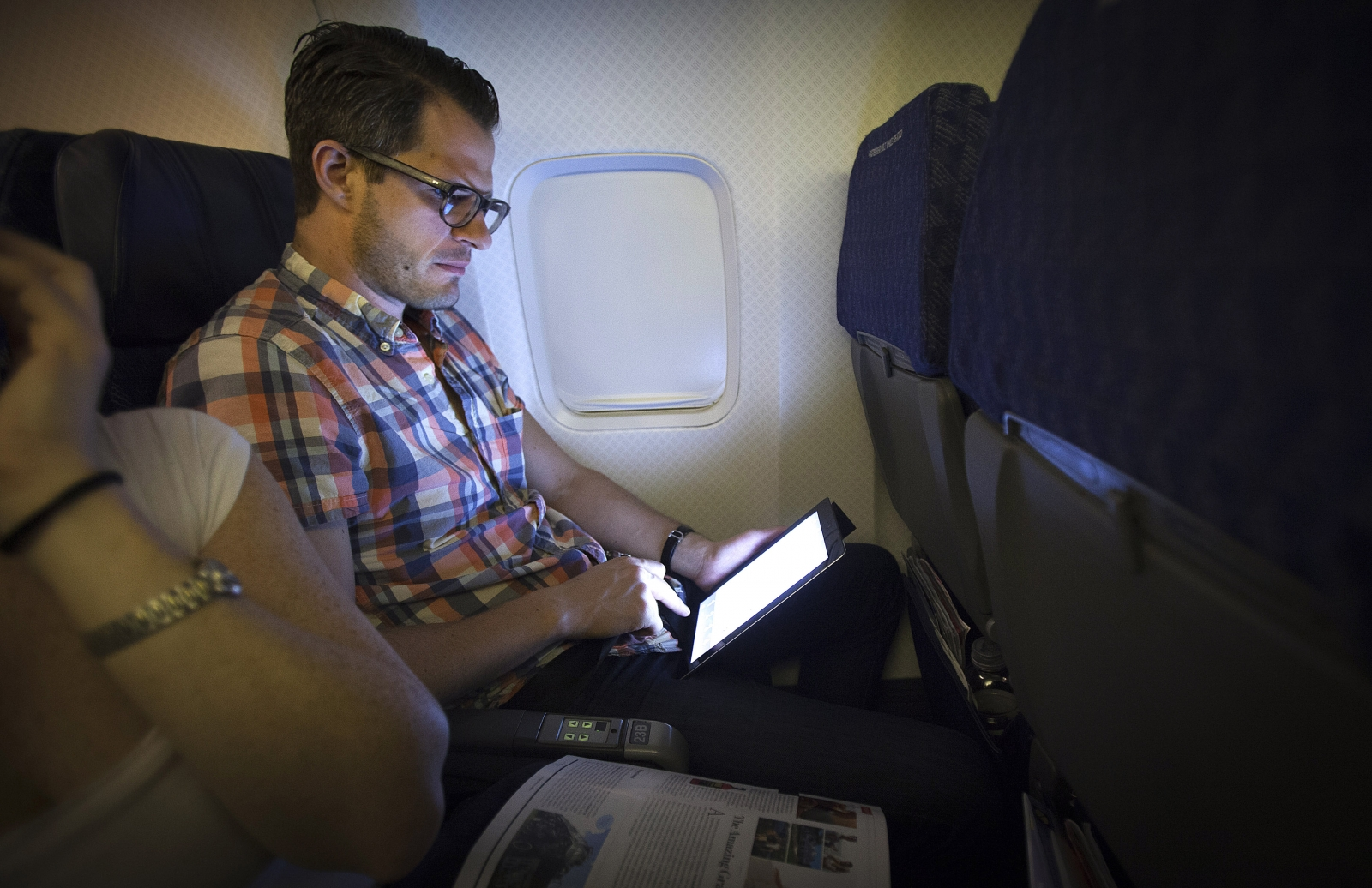 Man using tablet on an airplane