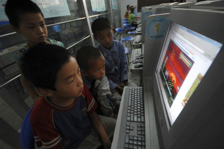 Chinese children play online games at internet cafe.