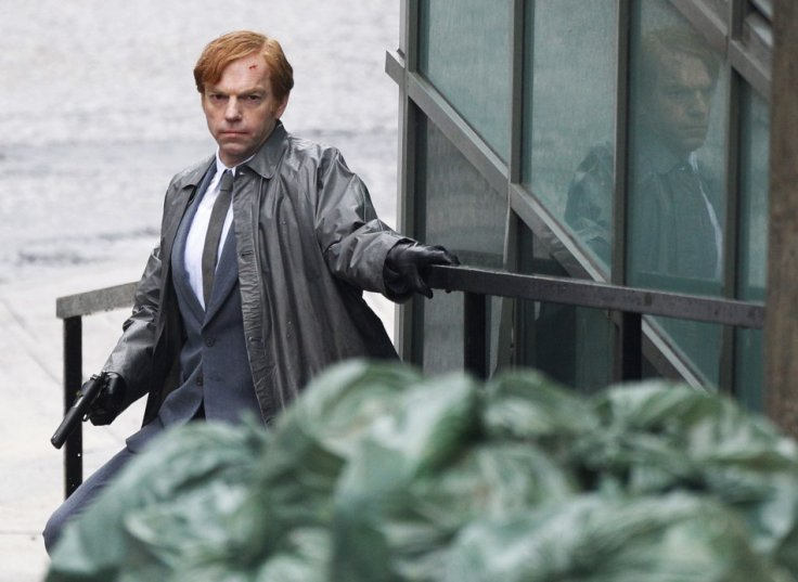 "Actor Hugo Weaving crouches as he holds a gun during filming of ""Cloud Atlas"" in Glasgow, Scotland"