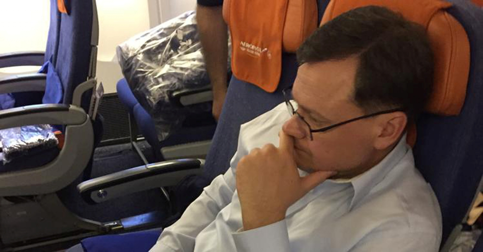 Evgeny Buryakov, a former New York banker who was convicted in federal court of conspiring to act in the United States as an agent of the Russian Federation, is shown in this handout photo sitting on a commercial flight, escorted by deportation officers a