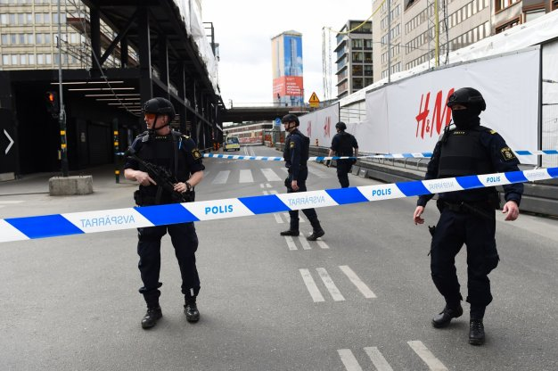 Police officers cordon off the scene where a truck crashed into the Ahlens department store at Drottninggatan in central Stockholm