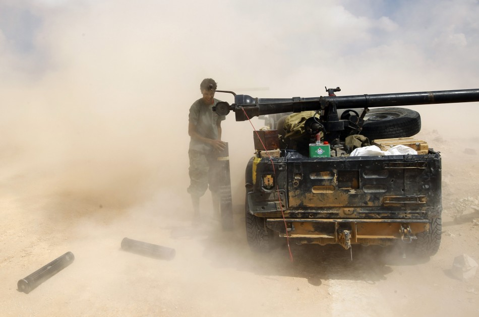 An anti-Gaddafi fighter loads a cannon near Sirte, the hometown of deposed leader Muammar Gaddafi