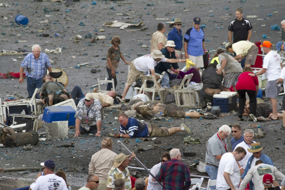People rush to help injured spectators following the crash of a vintage World War Two P-51 Mustang fighter plane near the grandstand at the Reno Air Races in Reno Nevada