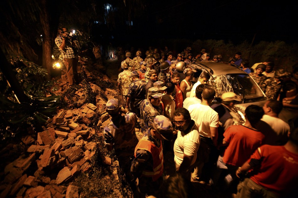 Members of the Nepalese army gather around a damaged car after the wall surrounding the British Embassy collapsed on top of the car that was passing by in Kathmandu