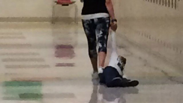 A teacher dragging a young student by the arm