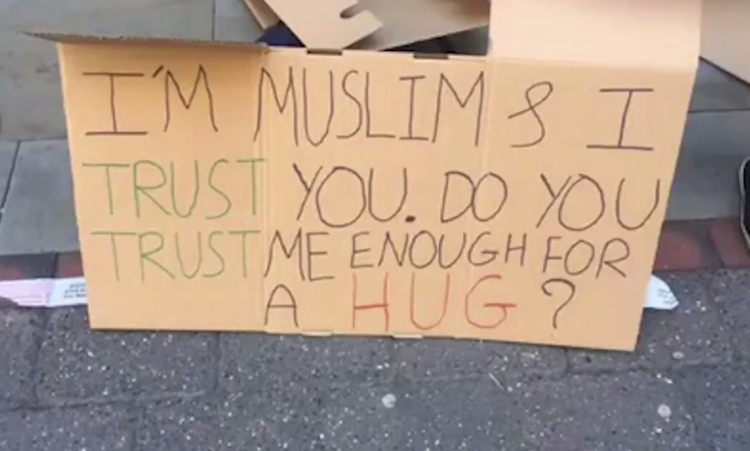 Blindfolded Muslim stands on the streets of Manchester offering hugs to strangers