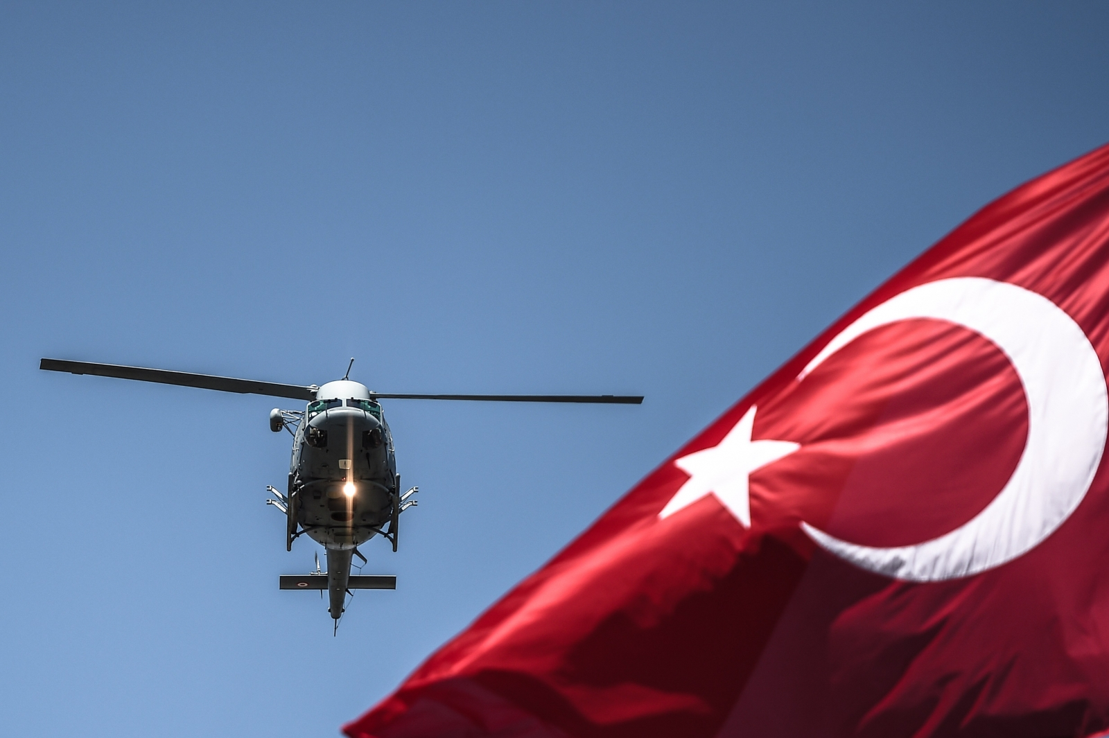 Turkish military helicopter flies behind flag