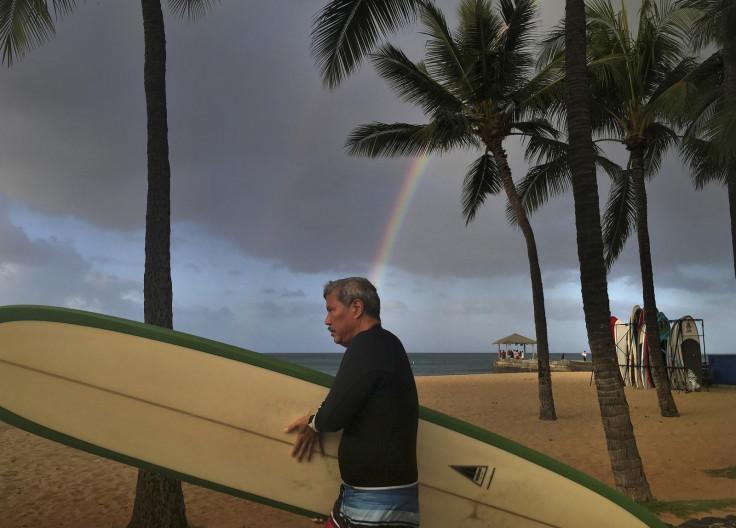 Surfers walks along the beach in Hawaii