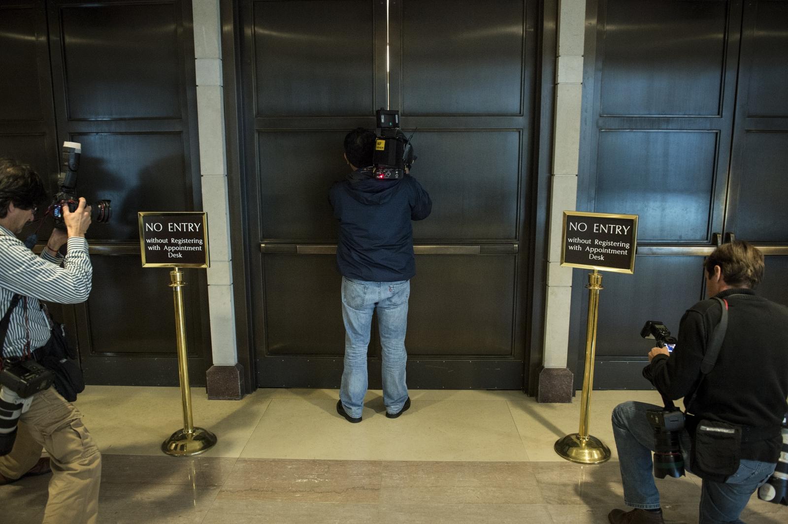 Cameraman tries to see through door crack