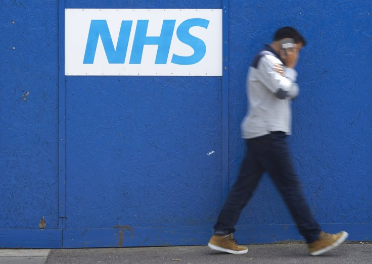 Man walking past NHS sign