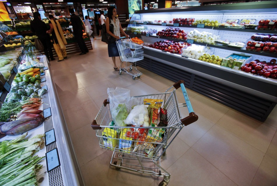 A trolley laden with fresh and processed food sits parked in an aisle as customers shop at a supermarket in Mumbai May 30, 2011.