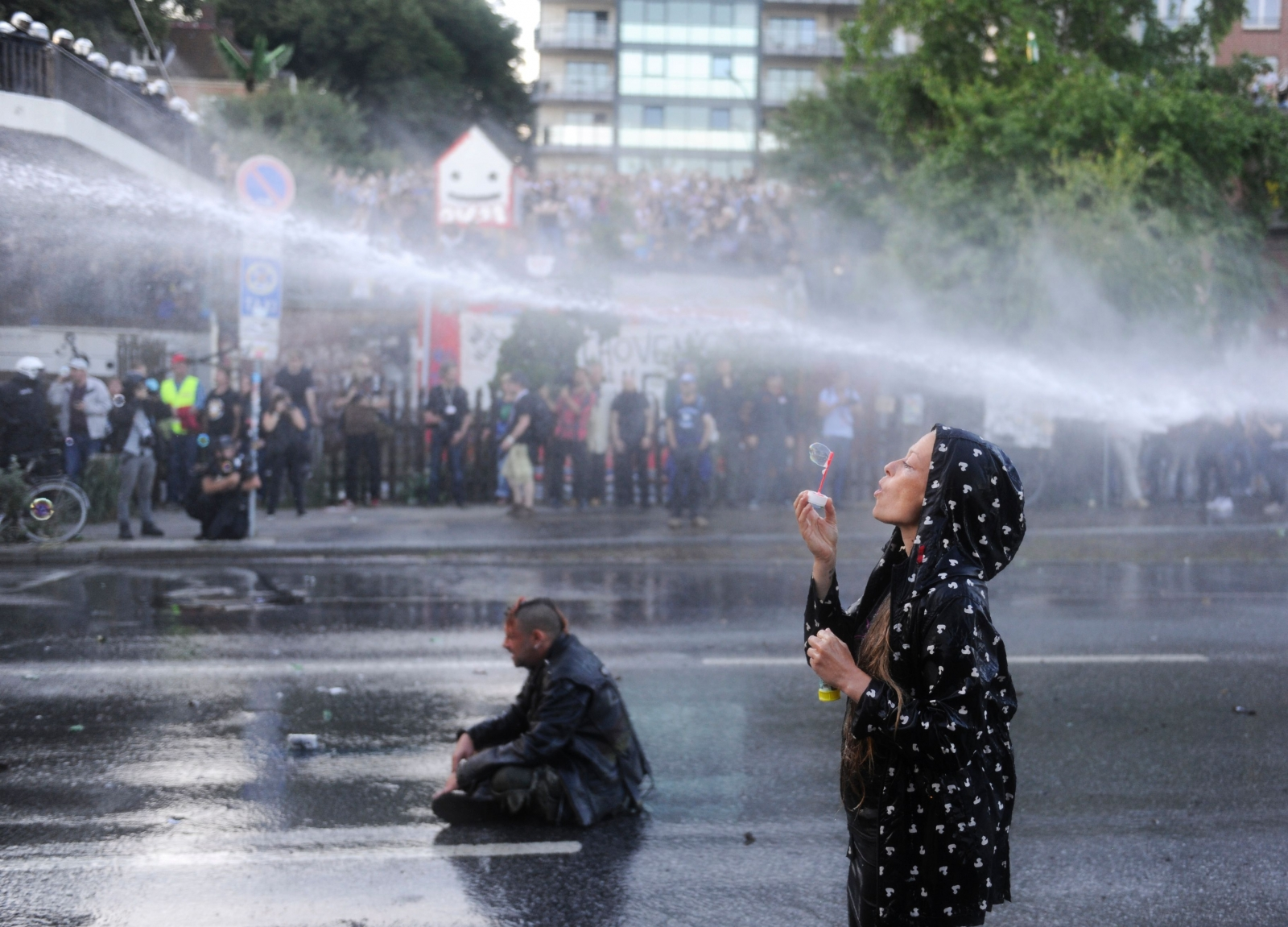 Protester blows bubbles under water cannon