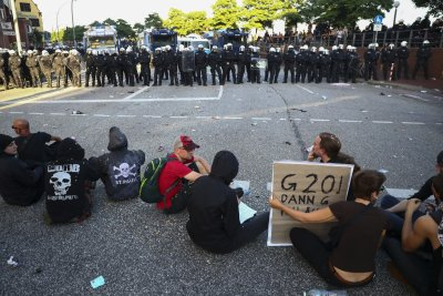Protesters sit in front of riot police