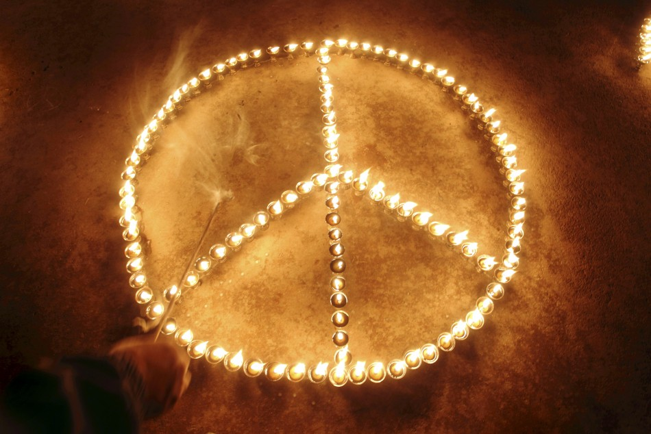Participant's hand is seen after lighting lamps to form peace sign to commemorate victims of Japan's March 11 earthquake and tsunami, at Boudhanath Stupa in Kathmandu