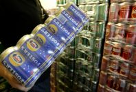 A customer carries Fosters beer cans from the cool room at a liquor store in Melbourne