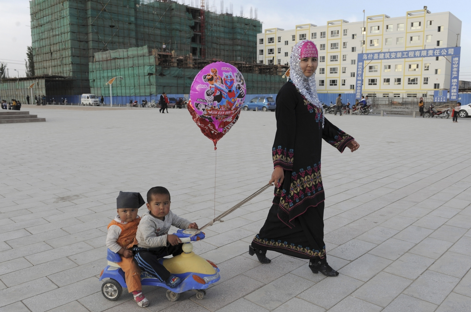 A Uighur woman pulls a buggy carrying her sons as she walks past residential buildings under construction in Uqturpan county, Xinjiang