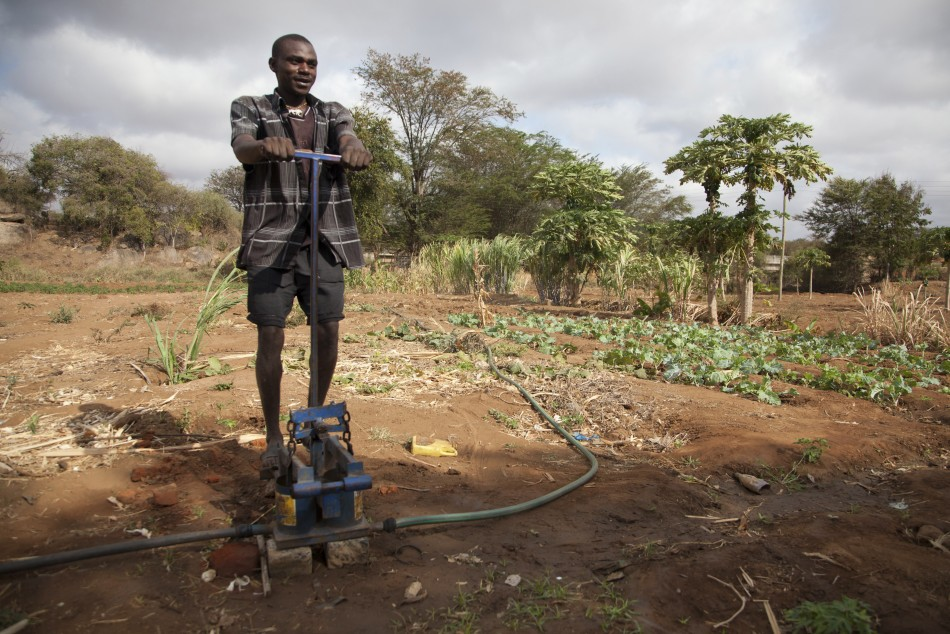 A farmer uses a foot pump to irrigate his crops in Mwingi