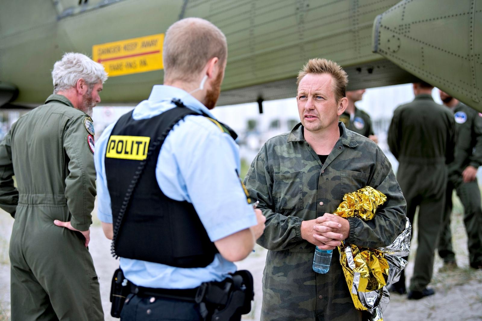 Danish submarine owner and inventor Peter Madsen talks to Danish police in Dragor Harbor south of Copenhagen, Denmark