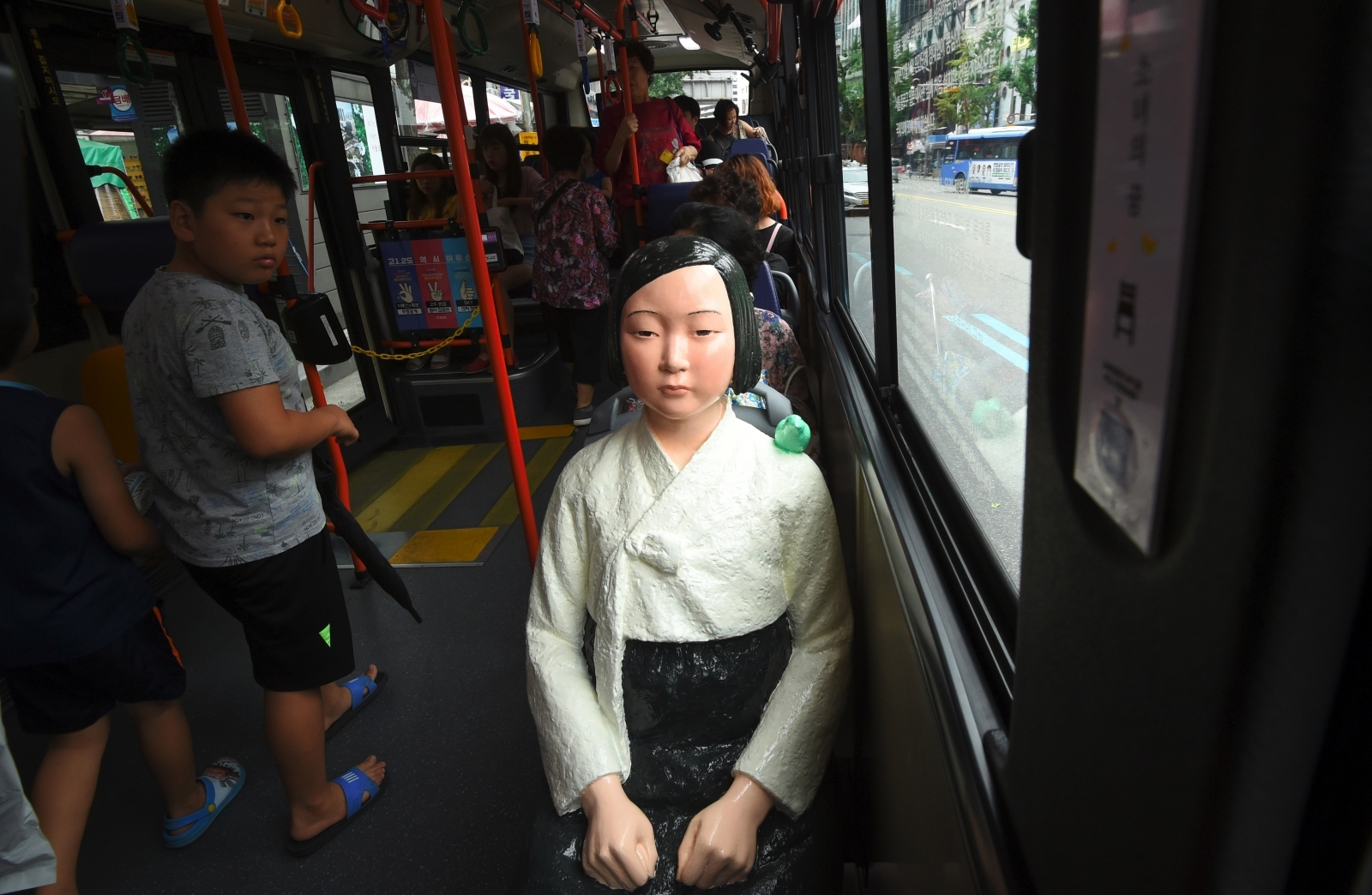 A boy (L) looks at a statue (R) of a teenage girl symbolizing former 'comfort women' who served as sex slaves for Japanese soldiers during World War II, placed on a bus running through downtown Seoul on August 14, 2017.