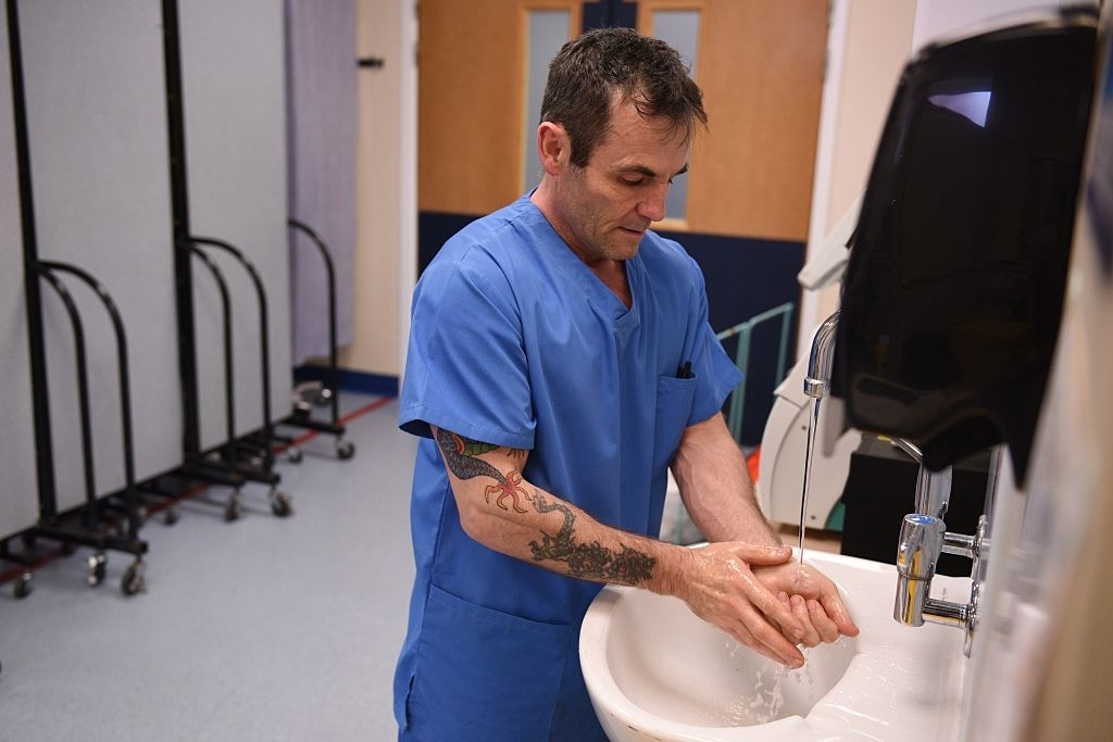 Hospital worker washes hands
