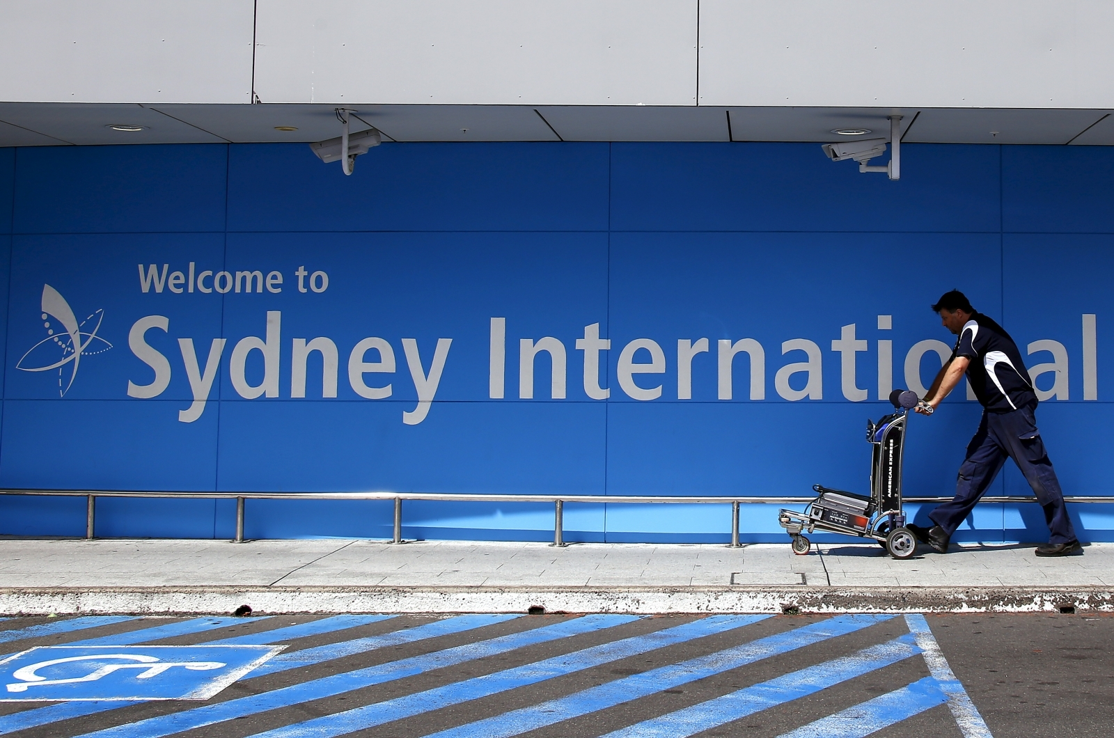 A passenger pushes a trolley as he walks towards the departures area at Sydney International Airport, Australia,