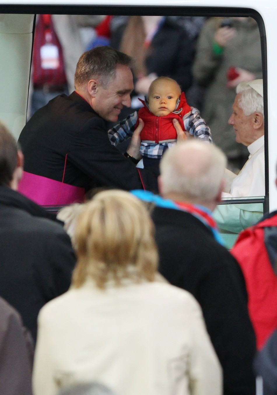 A baby boy is lifted into the Popemobile to meet Pope Benedict XVI as the pontiff arrives to conduct a Holy Eucharist at the Olympic stadium in Berlin