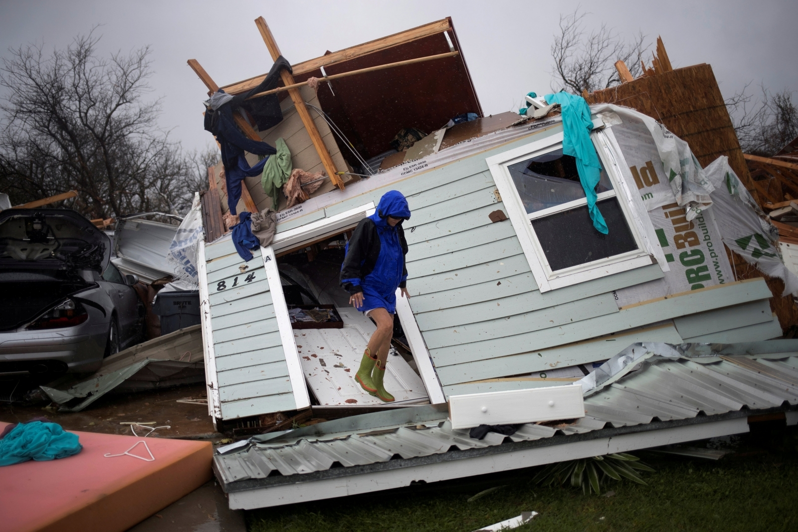 Woman stands on her front door as she surveys her property devastated by Hurricane Harvey in Rockport, Texas