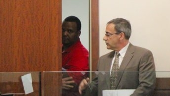 Joshua Hubert (partially behind door) is accused of throwing a seven-year-old girl off a bridge after kidnapping her