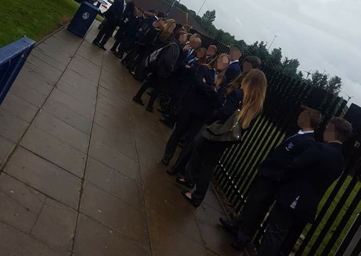 Pupils Kepier School in Sunderland line up in the rain to have their school uniforms inspected