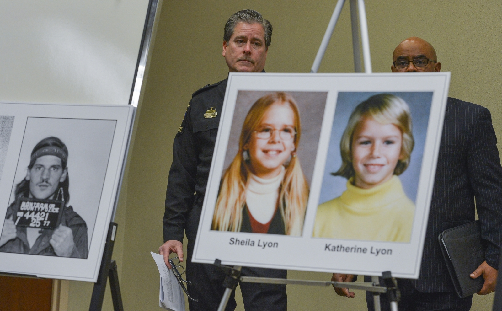 Montgomery County Police Captain Paul Starks, left, and Captain Marcus G. Jones stand behind a mug shot of Lloyd Lee Welch, Jr., who has now pleaded guilty to the murder of Katherine and Shelia Lyon, right, during a press conference in February 2014 in Ga