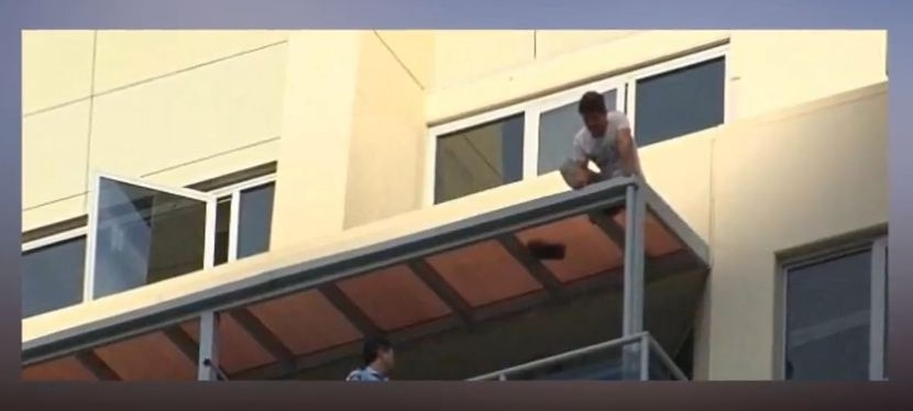 Man dangling off rooftop in Sydney