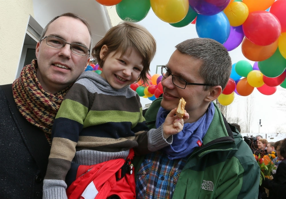 Berlin gay couple Kai (L) and Michael Korok and their daughter Jana