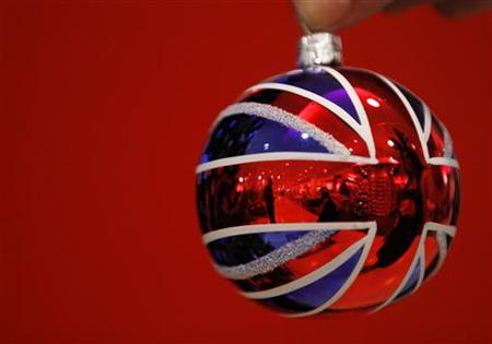 Selfridges employee Anisha Rethdawala poses with a Union flag themed tree ornament in Selfridges Christmas shop as it opens for business 145 days ahead of Christmas Day in central London