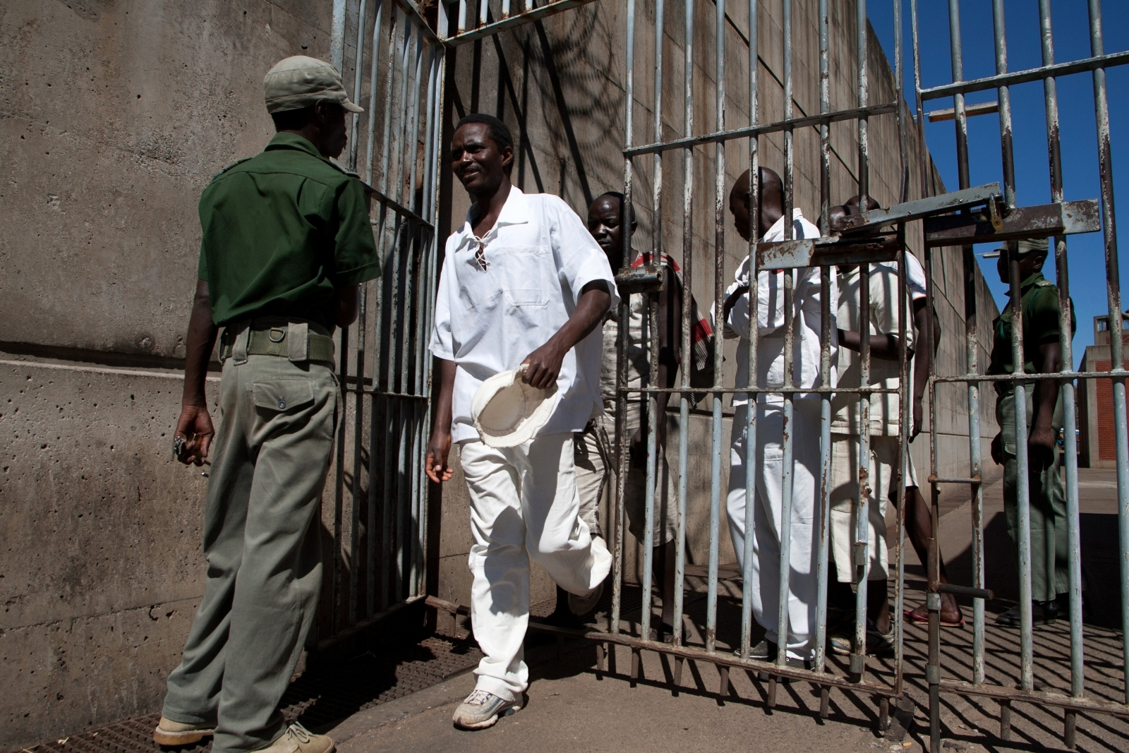 Prison Inmates walk past a prison guard at the Chikurubi Maximum security prison in Harare, where the country's hangman is expected to be based