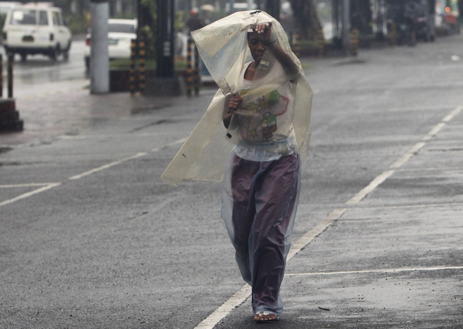 A woman uses a sheet of plastic to protect herself from rain brought by typhoon Nesat while walking along a main street in Manila