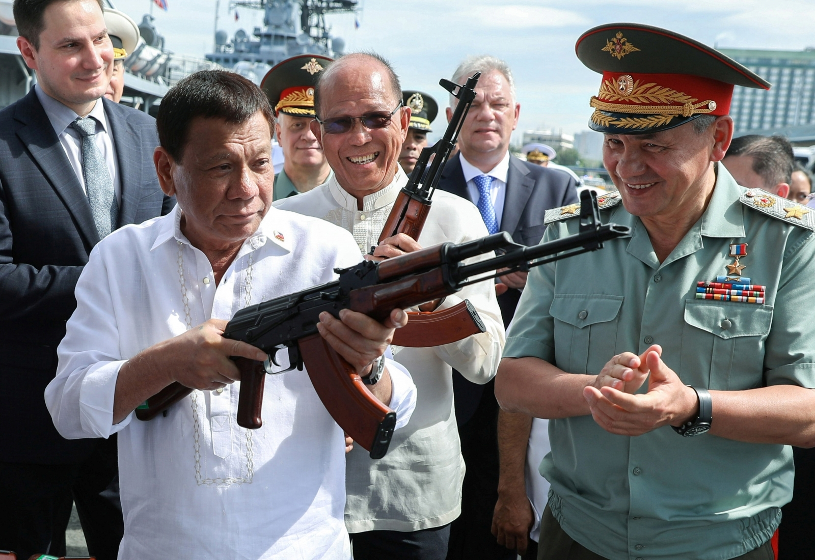 Philippine President Rodrigo Duterte (l) holds a AK-47 assault rifle as Russian Minister of Defence Sergei Shoigu looks